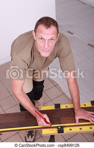 Man at home cutting wooden flooring to size - csp8499126