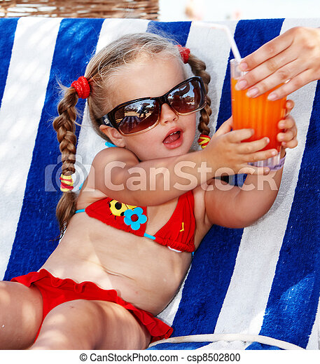 Child girl in glasses and red bikini drink juice. - csp8502800