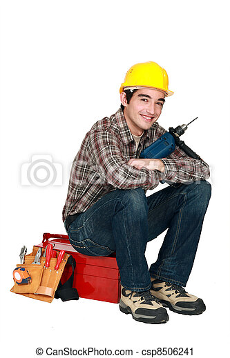young craftsman holding a drill and sitting on a tool box - csp8506241