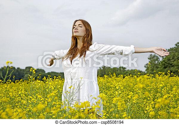 Beautiful woman in a yellow flowers field - csp8508194