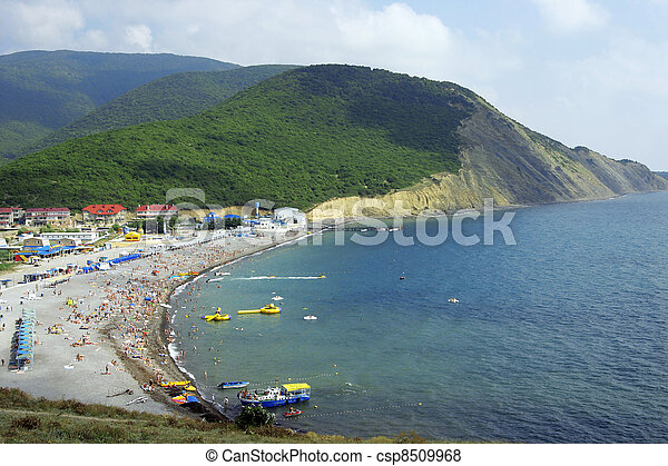 Sea bay, beach with people and constructions in an environment of mountains and the blue sky - csp8509968