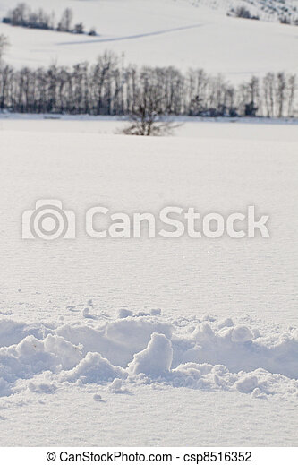 Close up of snow, with wood on the background