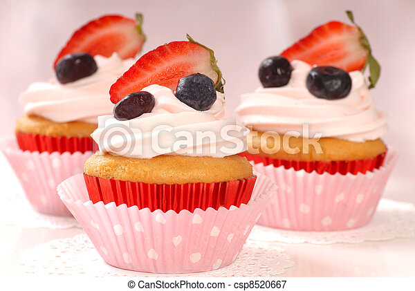 Delicious vanilla cupcake with strawberry frosting and fresh strawberries and blueberries - csp8520667