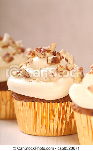 Delicious carrot cake cupcakes with cream cheese frosting and chopped pecan nuts - csp8520671