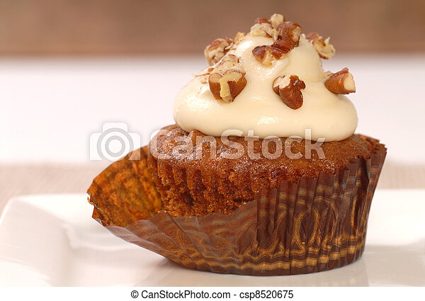 Delicious carrot cake cupcake with cream cheese frosting and chopped pecan nuts - csp8520675