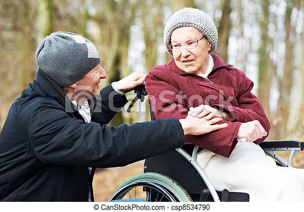 old senior woman in wheelchair with careful son - csp8534790