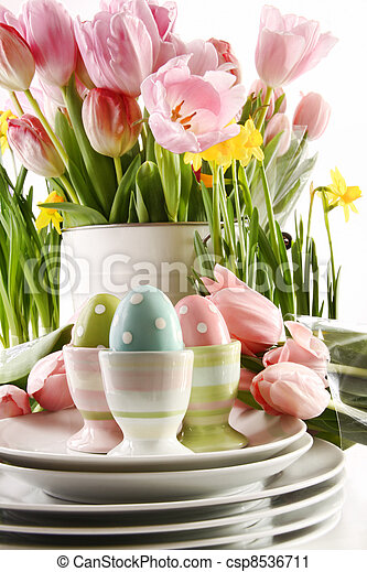 Easter eggs in cups with spring flowers on white - csp8536711