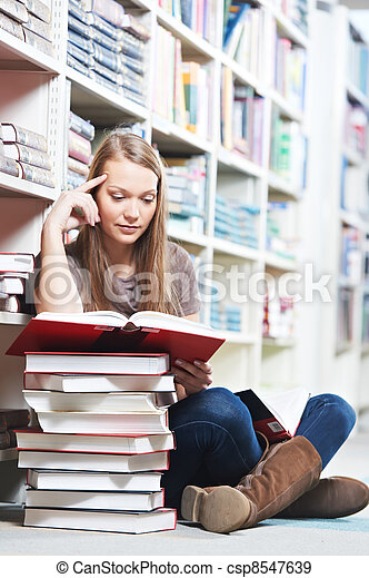 Smiling young adult woman reading  book in library - csp8547639