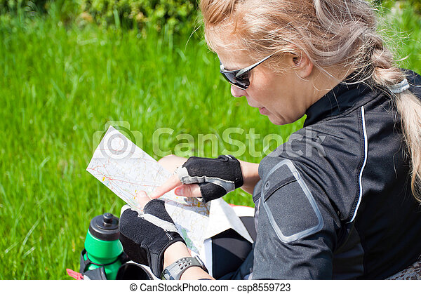 Woman on bicycle trip checking a map - csp8559723