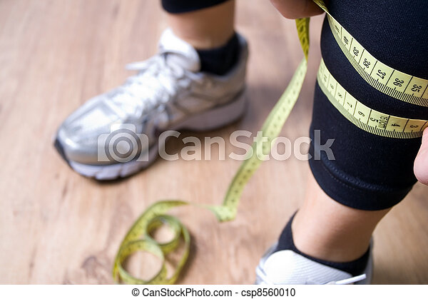 Woman measures a leg with centimeter after running at gym - csp8560010