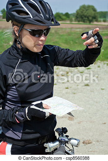 Woman on bicycle checking a map - csp8560388