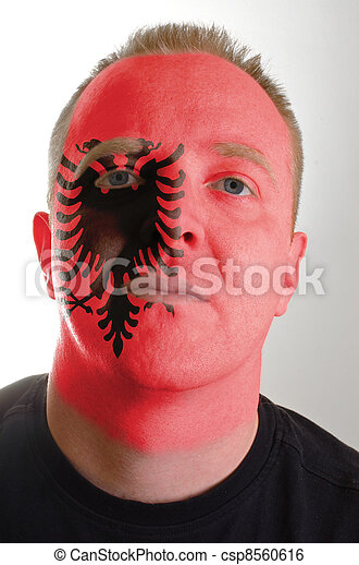 Face of serious patriot man painted in colors of albania flag - csp8560616