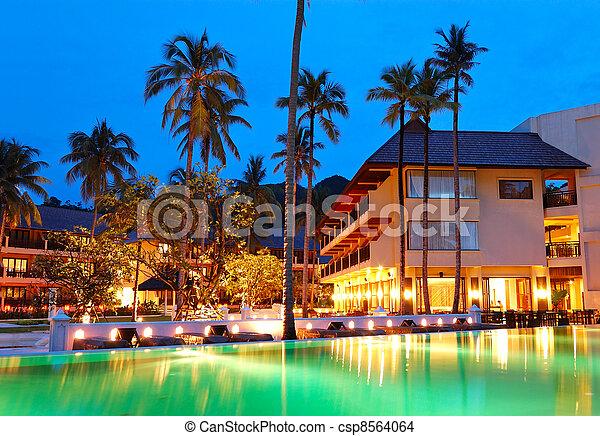 Green swimming pool near open-air restaurant in night illumination, Koh Chang island, Thailand - csp8564064