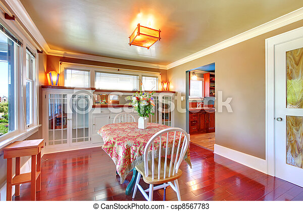 Beautiful dining room with shiny cherry hardwood. - csp8567783