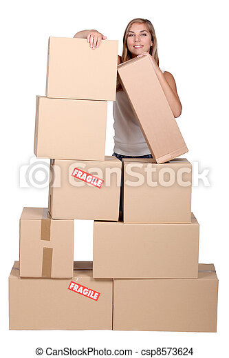 Young woman with a pile of cardboard boxes marked fragile - csp8573624