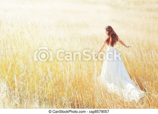 woman walking in the sunny meadow on summer day touching grass - csp8579057