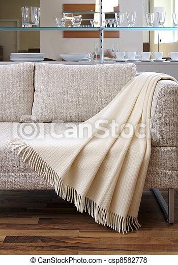 Cream throw draped over a settee - csp8582778