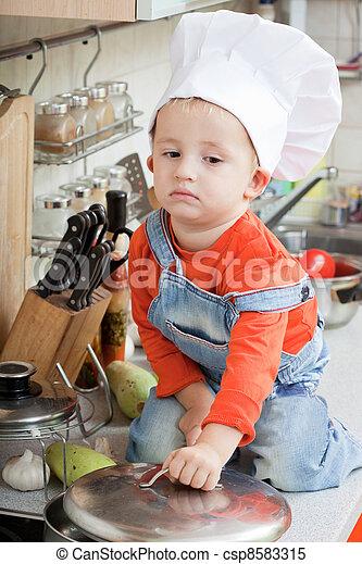 amusing kid in a chef cap on kitchen - csp8583315