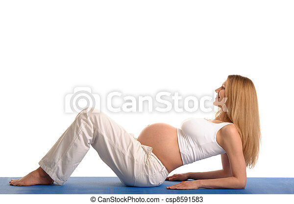 pregnant woman lying down and practicing yoga - csp8591583