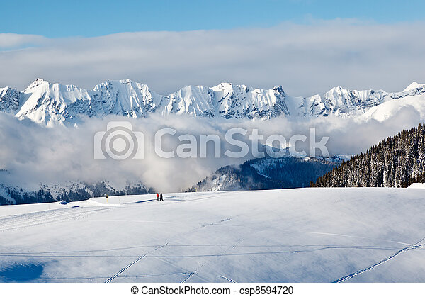Panoramic View on Mountains and Two People Trekking in French Alps in Winter - csp8594720