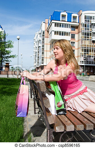 Girl with shopping bags relaxing on the bench