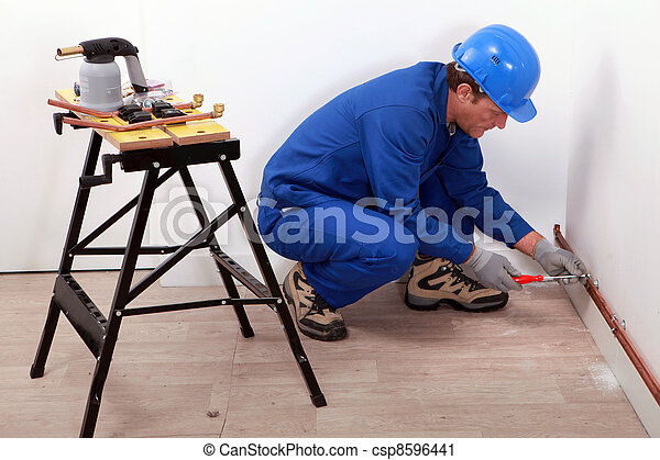 Plumber fitting copper pipes to a wall - csp8596441