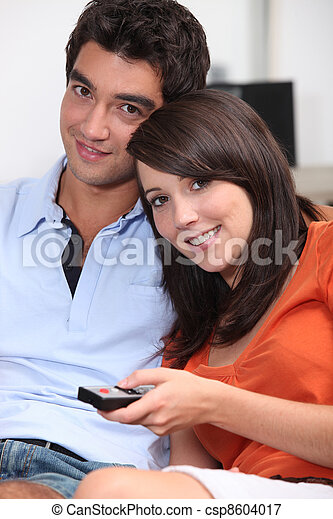 Young couple watching TV with a remote control - csp8604017