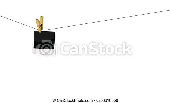 photo prints hanging on string - csp8618558