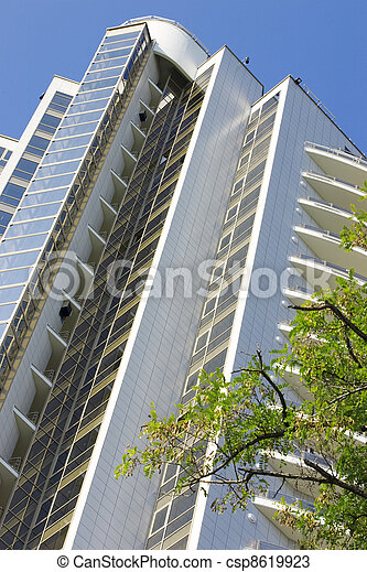 modern residential building with beautiful glass balconies on a background blue sky - csp8619923