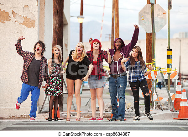 A group of young angry punk rock teens shout across the street. - csp8634387