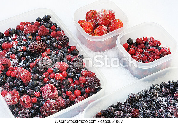 Plastic containers of frozen mixed berries in snow - red currant, cranberry, raspberry, blackberry, bilberry, blueberry, black currant, strawberry - csp8651887