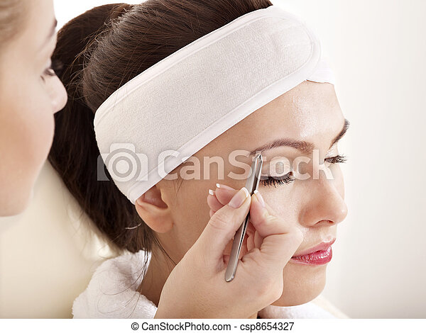 Tweezing eyebrow by beautician. - csp8654327