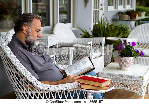 Man Reading Bible On Porch - csp8655157