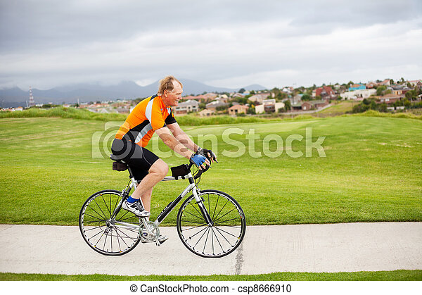 active senior man riding a bicycle - csp8666910