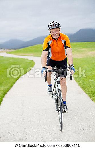 active senior man riding a road bicycle - csp8667110