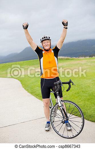 cheerful active senior man arms up - csp8667343