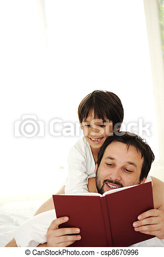 Father and son in bed, reading book together - csp8670996