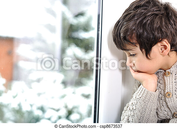 Sad kid on window cannot go out because of cold and snow - csp8673537