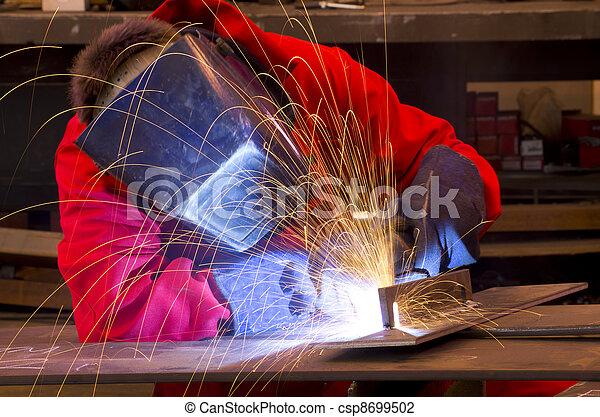 Welder in red overalls creates sparks.    - csp8699502