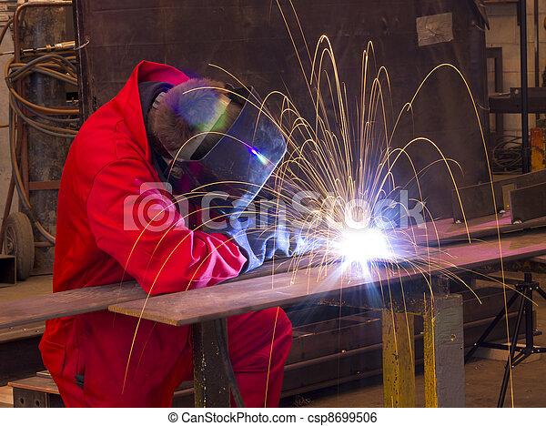 Welder bends to cut metal beam with orange sparks.