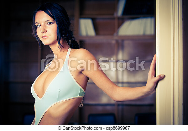 Alluring brunette wearing swimsuit and standing in an office - csp8699967