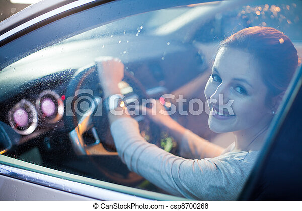 Pretty young woman driving her brand new car - csp8700268