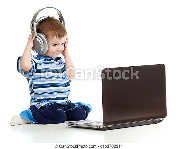 Funny child playing with laptop and listening to music in headphones - csp8702311