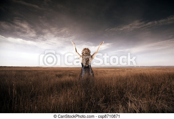 Woman lifting her hands up in a field - csp8710871