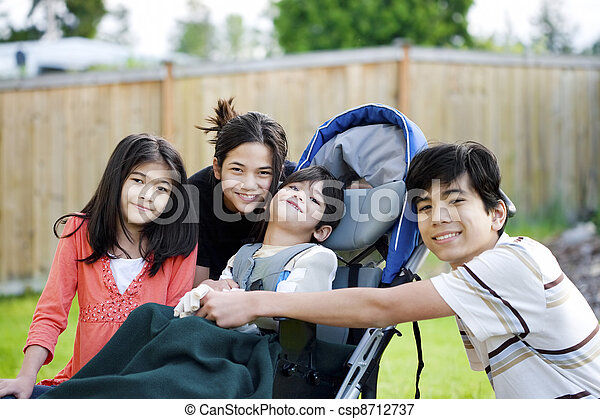Three children surrounding a small disabled child in wheelchair - csp8712737