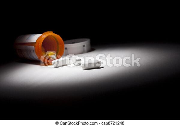Medicine Bottle and Pills Under Spot Light - csp8721248