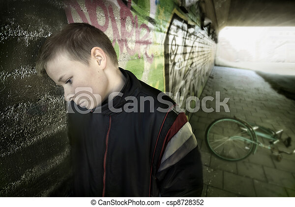 upset boy leaning against a wall - csp8728352
