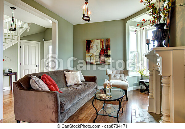 Elegant green living room with brown sofa and wood floor. - csp8734171