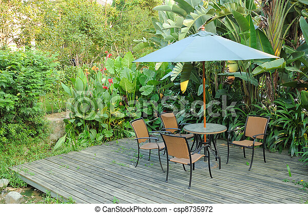 Garden furniture - rattan chairs and table under umbrella on a wooden floor by the banana trees background in garden - csp8735972