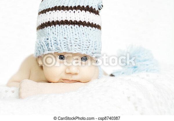 Newborn baby closeup portrait in blue woolen hat over white soft background. Indigo eyes - csp8740387